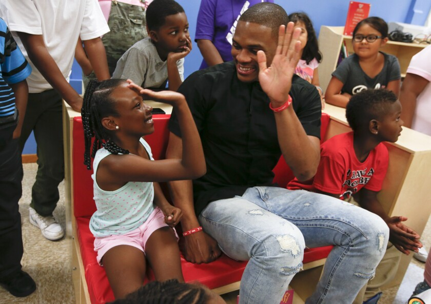 Oklahoma City Thunder star Russell Westbrook high-fives Haili-Ann McKinley after reading a book with her and Jayden Wade, right, at Manhattan Place Elementary School in Los Angeles. Westbrook opened reading rooms at three elementary schools during an area visit.