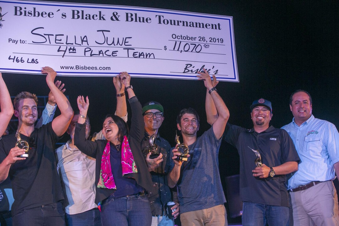 Team members of the Stella June and local dignitaries celebrate as they held up a giant check for $11,070, for a fourth place finish in the Bisbee Black & Blue marlin fishing tournament.