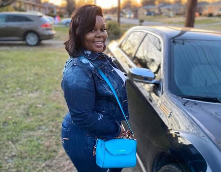 Breonna Taylor stands by a car in jeans and a denim jacket, carrying a blue purse.