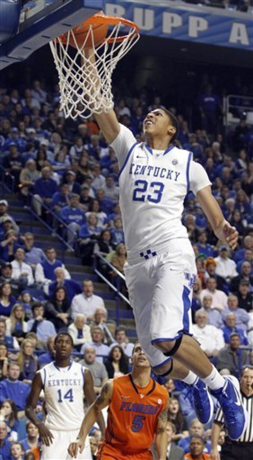 Kentucky's Anthony Davis (23) dunks the ball in front of Florida's Scottie Wilbekin (5) and Kentucky's Michael Kidd-Gilchrist (14) during the first half of an NCAA college basketball game in Lexington, Ky., Tuesday, Feb. 7, 2012. (AP Photo/James Crisp)
