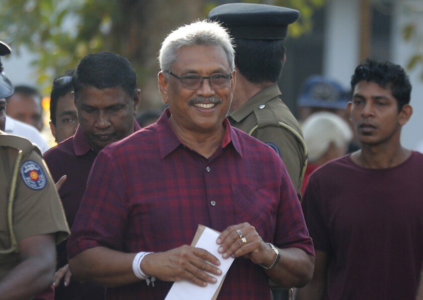 Sri Lanka's former Defense Secretary and presidential candidate Gotabaya Rajapaksa, center, leaves a polling station after casting his vote in Embuldeniya, on the outskirts of Colombo, Sri Lanka, Saturday, Nov. 16, 2019. Polls opened in Sri Lanka's presidential election Saturday after weeks of campaigning that largely focused on national security and religious extremism in the backdrop of the deadly Islamic State-inspired suicide bomb attacks on Easter Sunday. (AP Photo/Eranga Jayawardena)