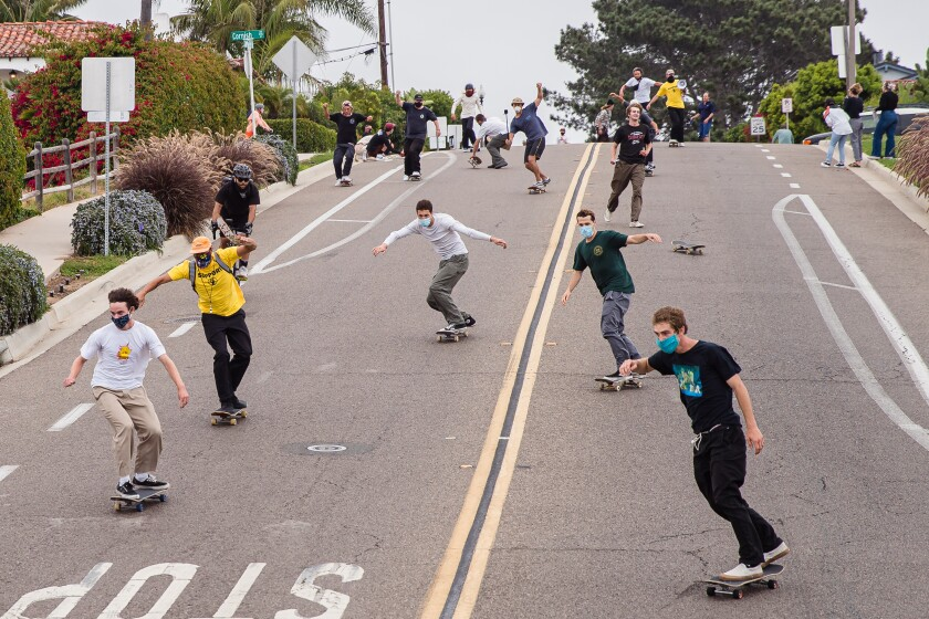 Skateboarders head down a hill on Santa Fe Drive in Encinitas for Sunday's Pushing for Peace protest.