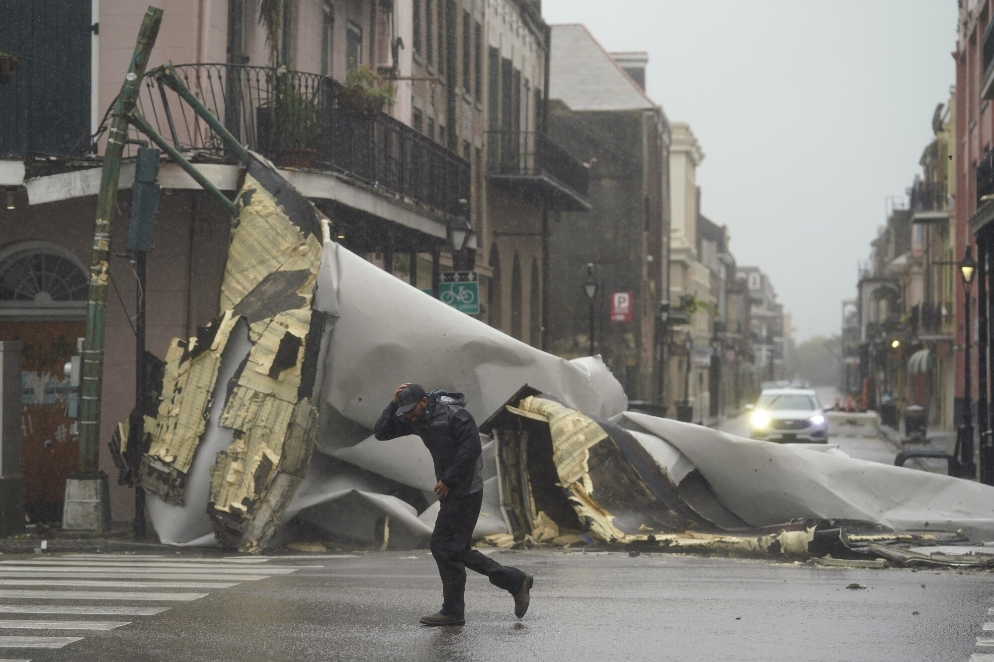 A man passes by a section of roof blown off a building.