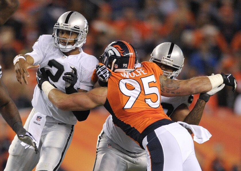 FILE - In this Sept. 23, 2013 file photo, Oakland Raiders quarterback Terrelle Pryor (2) is hit by Denver Broncos defensive end Derek Wolfe (95) after throwing a pass in the second quarter of an NFL football game, in Denver. Wolfe says he's finally healthy after suffering a seizure in November that