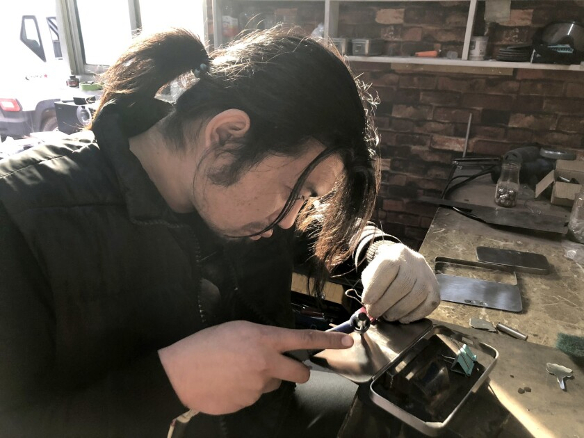 BEIJING CHINA NOVEMBER 21, 2018 -- Geng Shuai making clever cellphone case component in his workshop