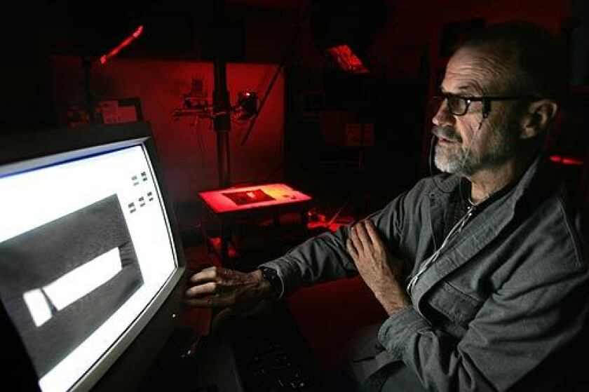 Megavision President Ken Boydston looks at a computer screen as LEDs in the background, emitting red light, illuminate a shard from the 10th century BC with the oldest Hebrew text ever discovered.