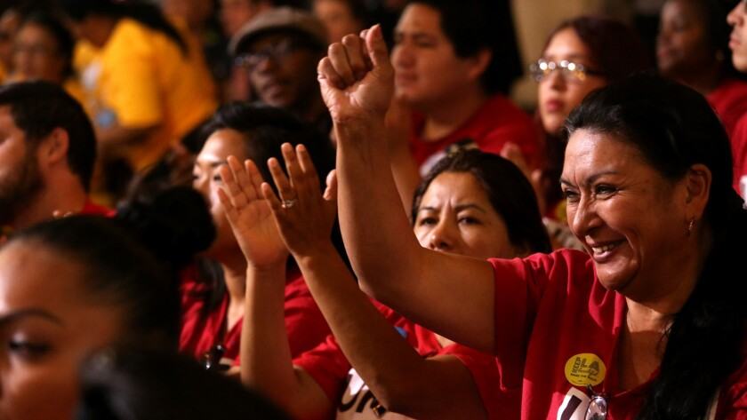 Audience members celebrate at a May 19 meeting where the Los Angeles City Council supported raising the city's minimum wage to $15 per hour.