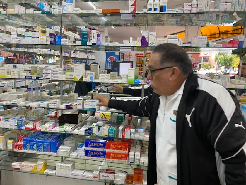 """In Tijuana, a pharmacist reaches for PulmonarOM, a medicine people have been buying """"like crazy"""" since the spread of the coronavirus began."""