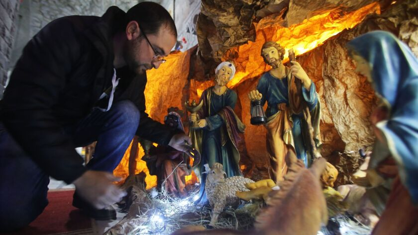 A Syrian man decorates the Saint Mary Church of the Holy Belt with a Christmas Nativity scene in the bombed-out city of Homs on Sunday.
