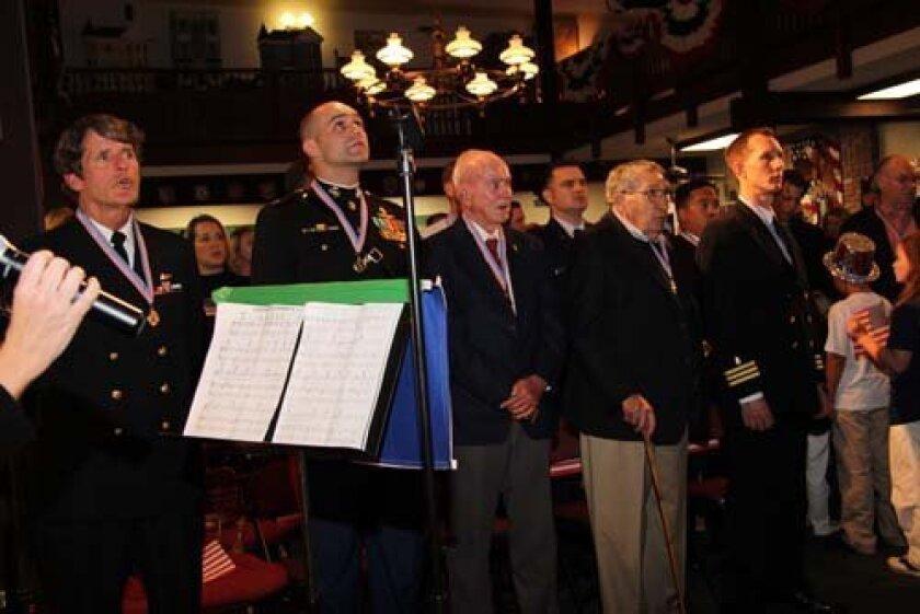 Veterans honored by The Evans School join in on patriotic songs.