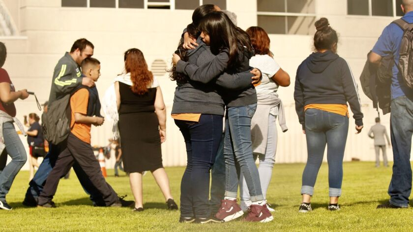 Students and families reunite after a shooting at Sal Castro Middle School in Westlake on Thursday. Two 15-year-olds were wounded by gunfire. A 12-year-old girl is in custody.