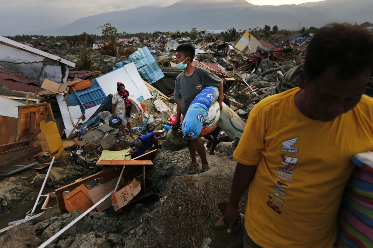 In this Friday, Oct. 5, 2018, photo, a family carries salvageable items they scavenged from the ruins of their house in the Petobo neighborhood which was wiped out by liquefaction caused by an earthquake in Palu, Central Sulawesi, Indonesia.