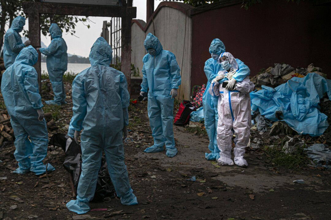 A woman wearing PPE, takes a glimpse of her husband's body, a victim of COVID-19, in Gauhati, India.