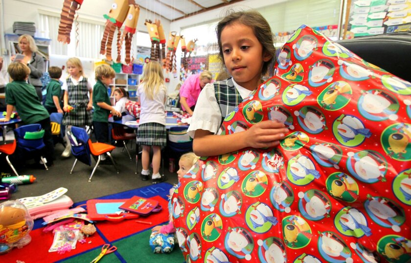 Haley Quejada carries a large stuffed animal that she wrapped Tuesday with other kindergartners at St. Patrick's Catholic School in Carlsbad. The holiday gifts, from students' own toy collections, will go to an orphanage in Mexico. Charlie Neuman • U-T