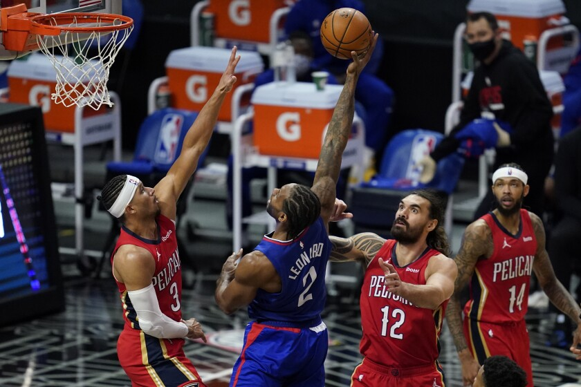 Clippers forward Kawhi Leonard shoots between New Orleans Pelicans guard Josh Hart and center Steven Adams.