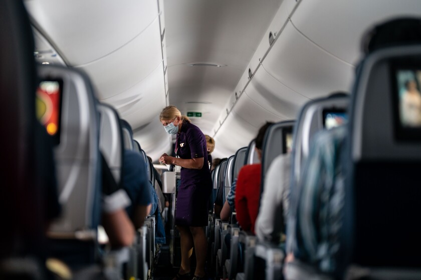 A masked flight attendant takes an order from a passenger on a plane.