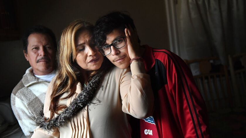 Student journalist Alex Medina, 16, right, poses with his parents Mario, left, and Candelaria at their home in Los Angeles.