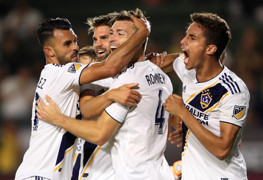 Galaxy defender Dave Romney (4) is congratulated by teammates after scoring against Tijuana.