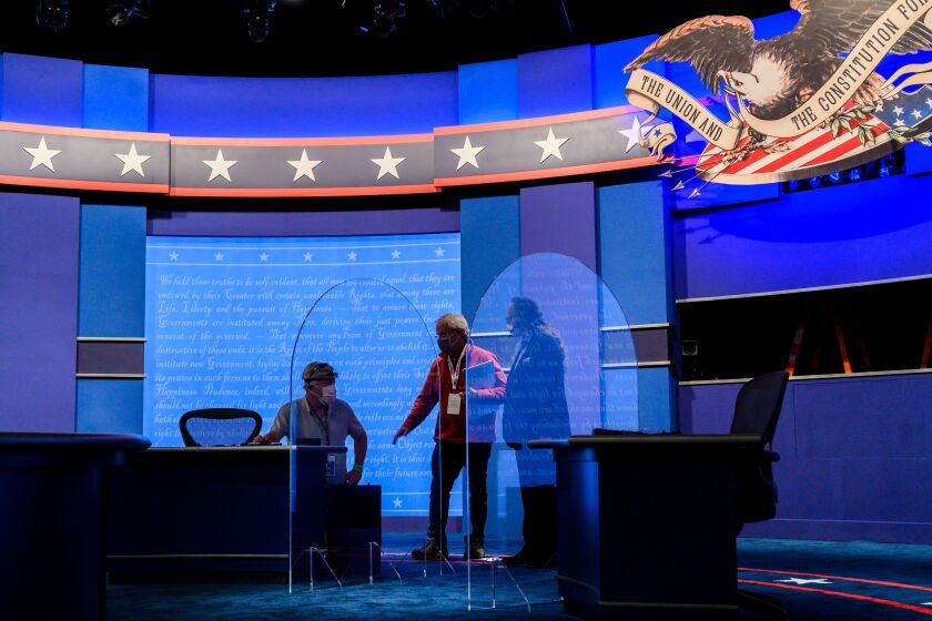 Workers install plexiglass protections on the stage of the debate hall ahead of the vice presidential debate