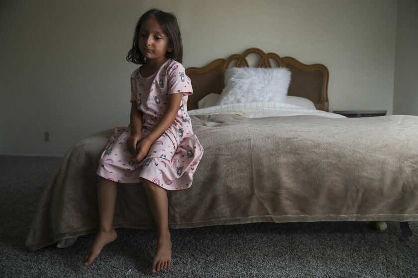 Afghan refugee Aqsa Sadat, 6, sits on a bed provided by members of the group Helping El Cajon Refugees.