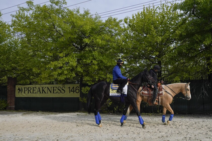 Exercise rider Humberto Gomez, top left, takes Kentucky Derby winner and Preakness entrant Medina Spirit to the track for a training session ahead of the Preakness Stakes horse race at Pimlico Race Course, Wednesday, May 12, 2021, in Baltimore. (AP Photo/Julio Cortez)