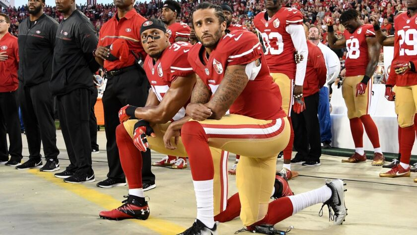 San Francisco's Colin Kaepernick, right, and Eric Reid kneel during the national anthem prior to a game against the Rams on Sept. 12, 2016.