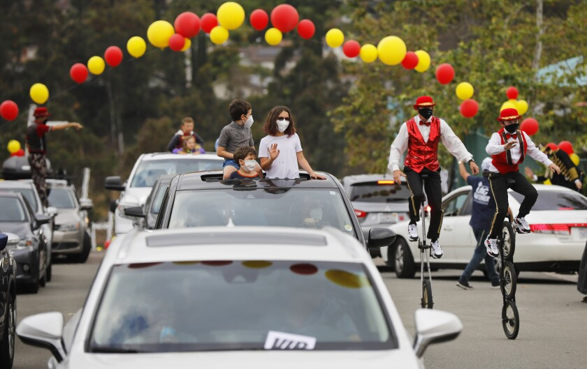 Families watch performers during a drive-thru circus to celebrate the Jewish holiday of Lag B'Omer at the Chabad San Diego campus in Scripps Ranch on May 12. Thousands of people attended the event that was complete with circus acts, live music, festival floats and a symbolic bonfire.