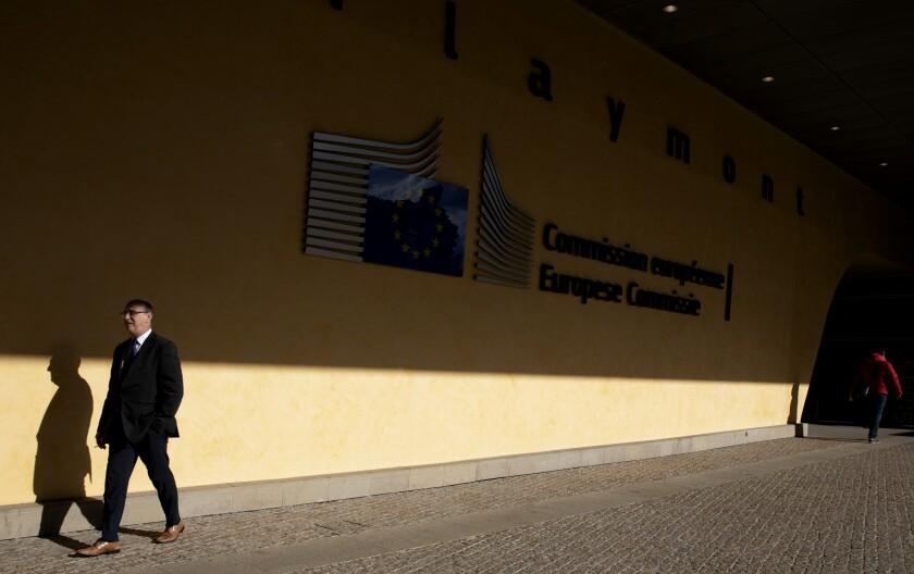 A man walks by the European Union logo outside EU headquarters in Brussels, Tuesday, Feb. 25, 2020. (AP Photo/Virginia Mayo)