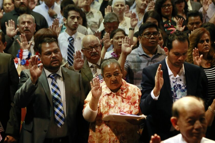 New citizens are sworn in during a naturalization ceremony at Golden Hall.