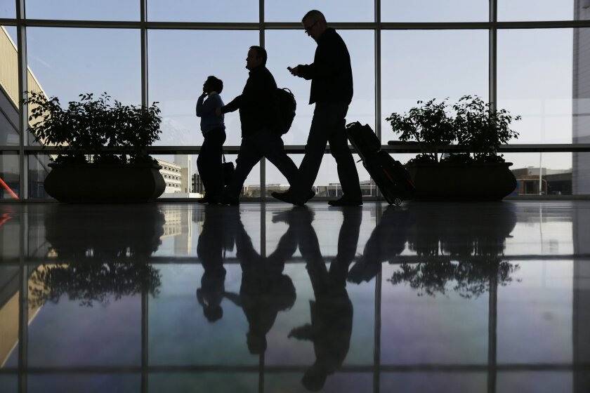 FILE - In this Feb. 14, 2013 file photo, Travelers pass through a corridor at Philadelphia International Airport in Philadelphia.  As the Justice Department launches an investigation into possible collusion in the airline industry, experts say the government faces the burden of proving that the car