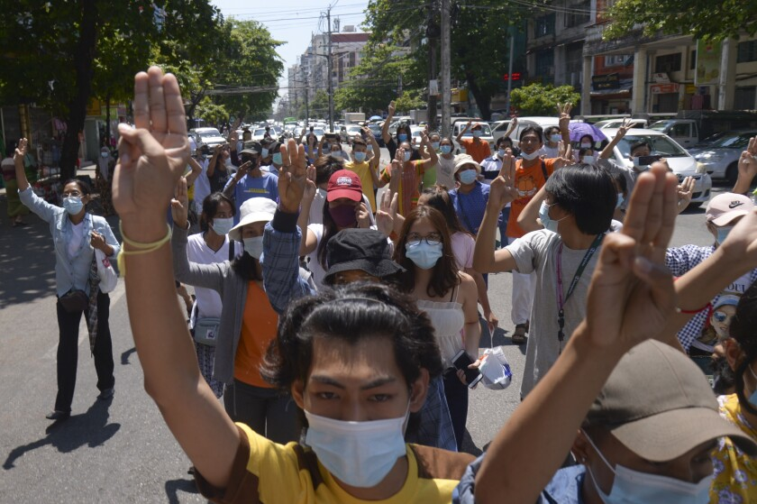 Anti-coup protesters flash the three-finger salute during a rally in Yangon, Myanmar on Tuesday May 4, 2021.