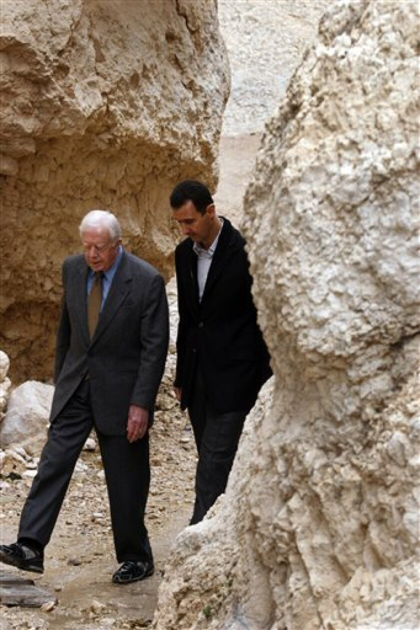 Syrian President Bashar Assad, left, and former U.S. President Jimmy Carter are seen on Sunday, Dec. 14, 2008, in the split mountain in the mountainous town of Ma�aloula, Arabic for entryway, some 56 kilometers to the northeast of Damascus, Syria. According to legend, St. Taqla was being pursued by soldiers of her father to capture her after she converted to Christianity, when she came upon this mountain which split open and let her through to escape. Carter is on a three-day visit to Damascus for talks on the prospects for peace in the Middle East.(AP Photo/Bassem Tellawi)