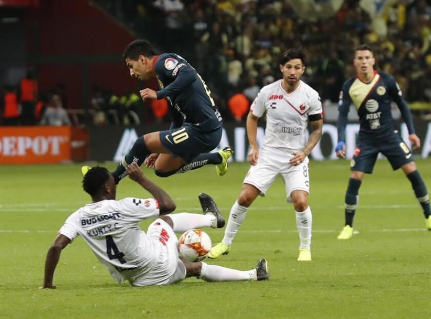 El jugador Cecilio Domínguez del América (arriba) disputa el balón con Luis Caicedo (abajo) del Veracruz durante un juego de la jornada 17 del Torneo Apertura en el estadio Nemesio Diez de la ciudad de Toluca (México). EFE