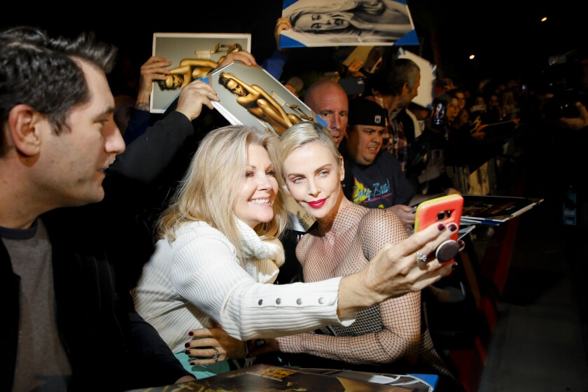 Charlize Theron poses for photos with movie fans at the Palm Springs International Film Festival Awards Gala