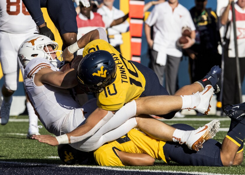 West Virginia linebacker Dylan Tonkery (10) tackles Texas quarterback Sam Ehlinger, left, who crosses the goal line during the first half of an NCAA college football game Saturday, Oct. 5, 2019, in Morgantown, W.Va. (AP Photo/Raymond Thompson)