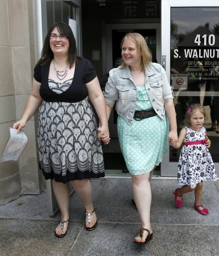 Heather, left, and Natalie Starr, with daughter Libby, smile after being married on the steps of the Outagamie County administration building on Monday, June 9, 2014, in Appleton, Wis. They are the first same-sex couple to be married in the county. (AP Photo/The Post-Crescent, William Glasheen)