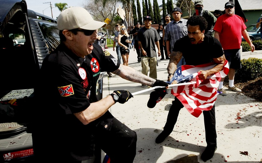 """A Ku Klux Klansman, left, struggles with a protester for an American flag after members of the KKK tried to start a """"White Lives Matter"""" rally at Pearson Park in Anaheim on Saturday. Three people were treated at the scene for stab wounds, and 13 people were arrested."""