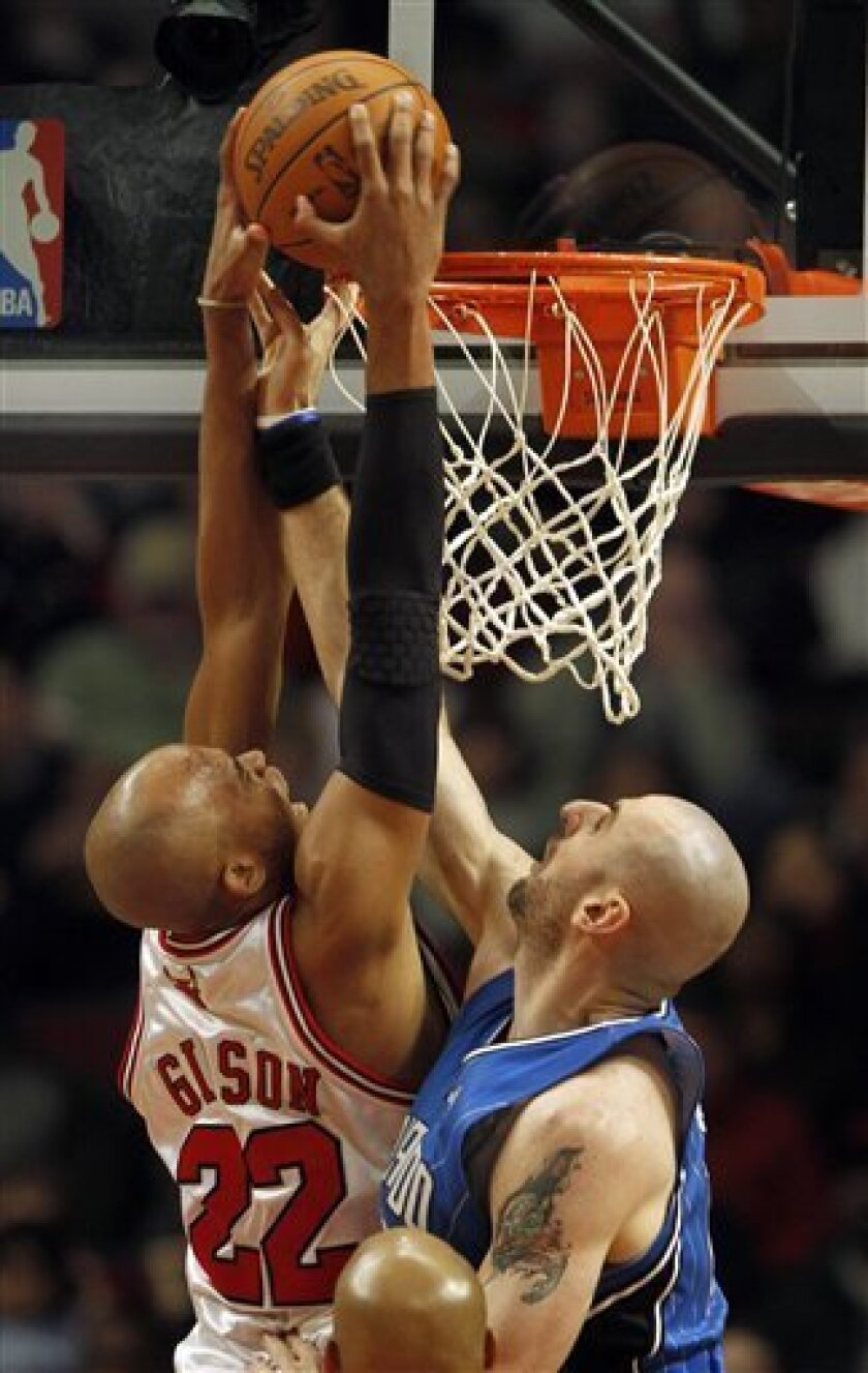 Chicago Bulls' Taj Gibson dunks over Orlando Magic's Marcin Gortat during the first half of an NBA basketball game on Saturday, Jan. 2, 2010, in Chicago. (AP Photo/John Smierciak)
