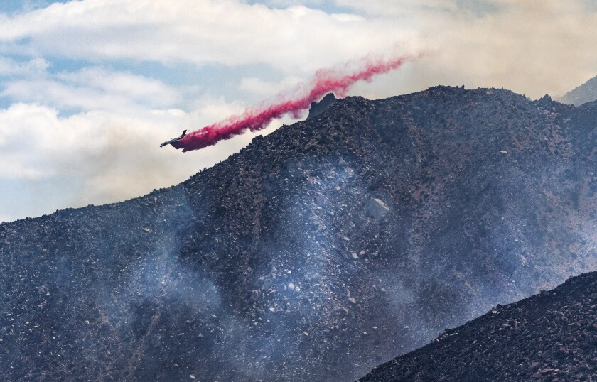 A firefighting plane drops retardant on the eastern flank of the Snow fire.