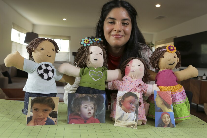 Ariella Pacheco shows the four dolls she made that mimic the unique characteristics of young people with medical issues