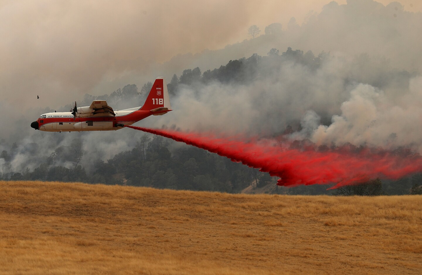 A firefighting air tanker drops fire retardant on a hillside ahead of the County Fire Monday in Esparto, California.