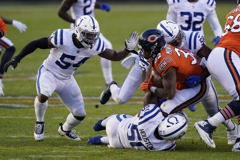 Chicago Bears' David Montgomery (32) is tackled by Indianapolis Colts' Justin Houston (50), Bobby Okereke (58) and Anthony Walker (54) during the second half of an NFL football game, Sunday, Oct. 4, 2020, in Chicago. (AP Photo/Nam Y. Huh)