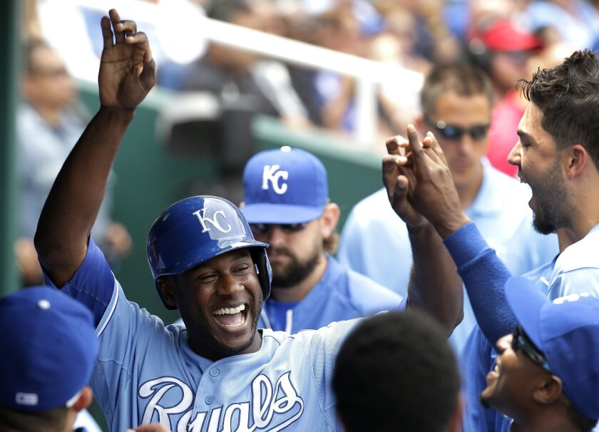 Kansas City Royals' Lorenzo Cain celebrates in the dugout after scoring on a single by Mike Moustakas during the second inning of a baseball game against the New York Yankees Sunday, June 8, 2014, in Kansas City, Mo. (AP Photo/Charlie Riedel)