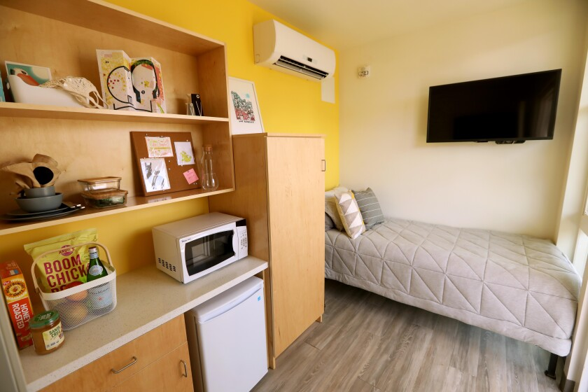 An interior view of a shipping container apartment shows a tidy room with a mustard-colored wall and a single bed
