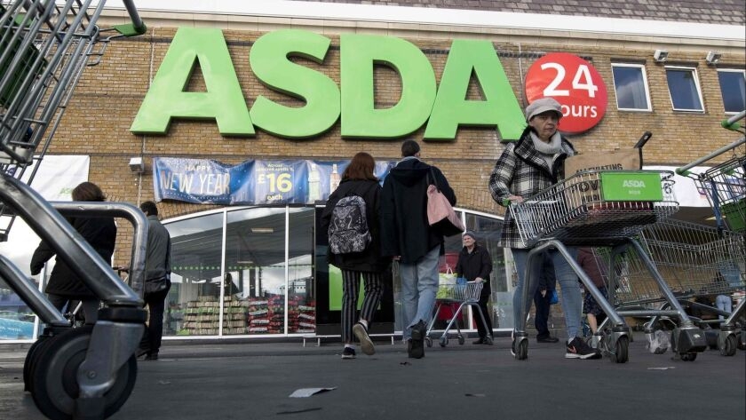 Customers come and go at a branch of Asda supermarket in south London on Jan. 10.