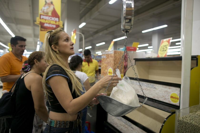 Tebie Gonzalez weighs rice as she shops for food at a supermarket in Cucuta, Colombia, Sunday, July 17, 2016, during a temporary opening of the long-closed border with Colombia.