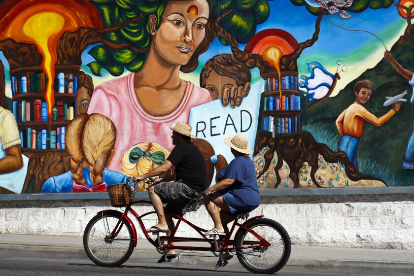 "An image of two people riding a bike past a colorful mural that shows a woman holding a sign that says ""Read"""