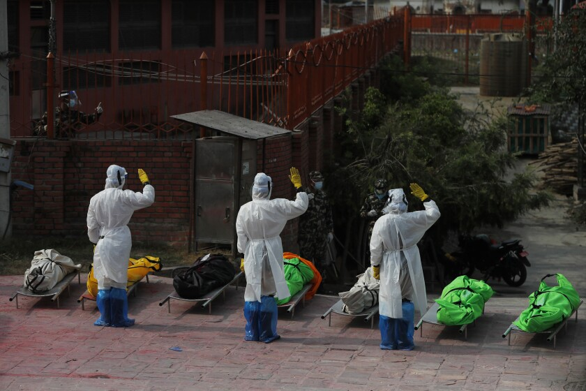 Nepalese army personnel in PPE suits salute to pay tribute to COVID-19 victims before cremating their bodies near Pashupatinath temple in Kathmandu, Nepal, Friday, May 7, 2021. Across the border from a devastating surge in India, doctors in Nepal warned Friday of a major crisis as daily coronavirus cases hit a record and hospitals were running out of beds and oxygen. (AP Photo/Niranjan Shrestha)