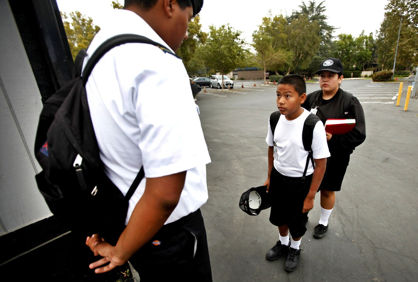 North Valley Military Institute sixth-grade student Joseph Ramirez, right, is inspected by 10th-grade student Robert Ramirez, left, before being allowed to enter the campus at the start of the school day on Oct. 2.