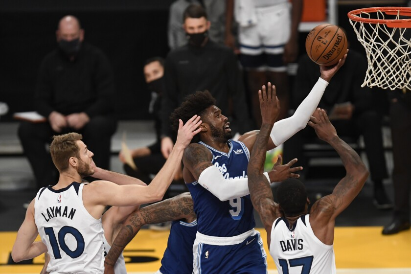 Lakers guard Wesley Matthews goes up for a basket over Minnesota Timberwolves forward Jake Layman and center Ed Davis.